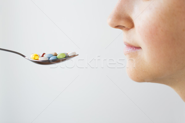 close up of female face and spoon with pills Stock photo © dolgachov