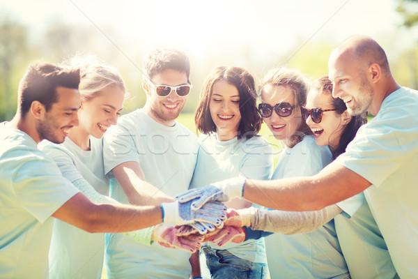 group of volunteers putting hands on top in park Stock photo © dolgachov