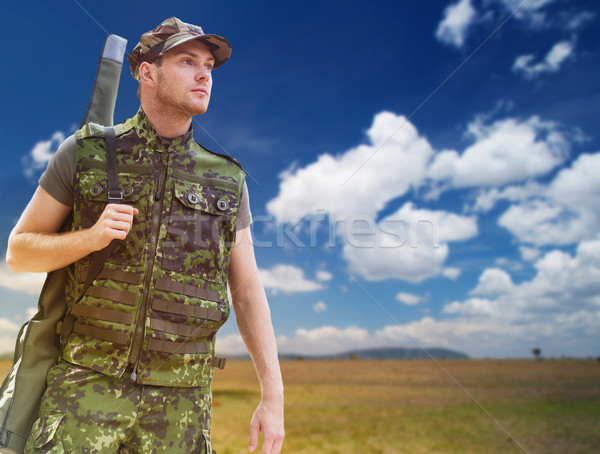 young soldier or hunter with gun over savannah Stock photo © dolgachov