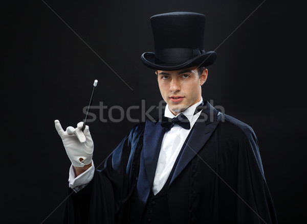Stock photo: magician in top hat with magic wand showing trick