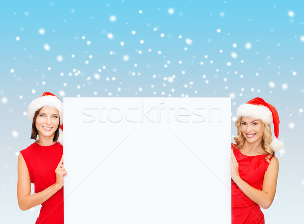 women in santa helper hats with blank white board Stock photo © dolgachov