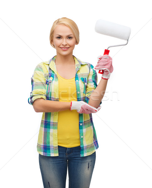 smiling woman in gloves with paint roller Stock photo © dolgachov
