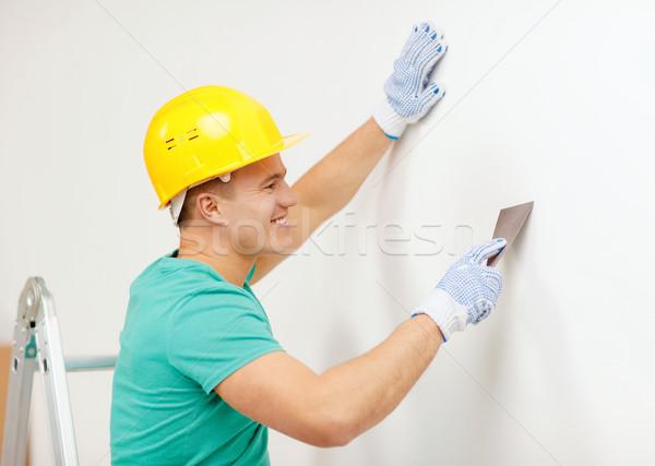 smiling man in helmet doing renovations at home Stock photo © dolgachov