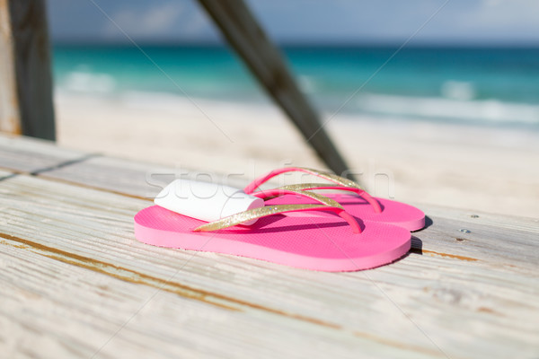 close up of sunscreen and slippers at seaside Stock photo © dolgachov
