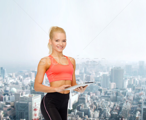 smiling sporty woman with tablet pc computer Stock photo © dolgachov