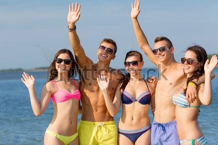 group of smiling women photographing on beach Stock photo © dolgachov