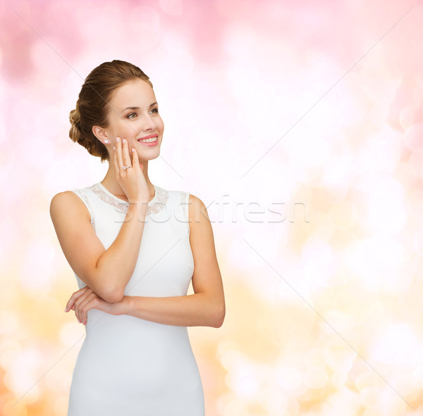 smiling woman in white dress wearing diamond ring Stock photo © dolgachov