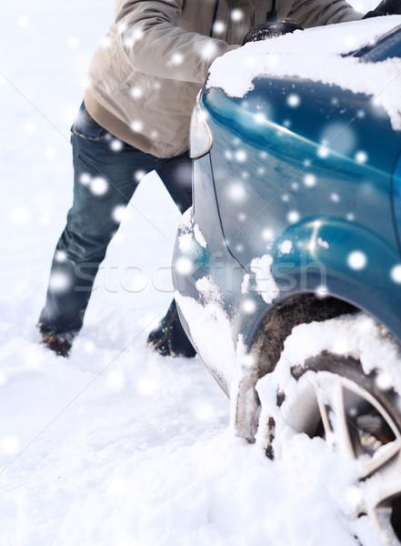 Stock photo: closeup of man pushing car stuck in snow