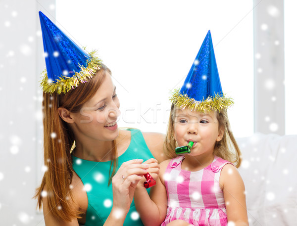 mother and daughter in party hats with favor horns Stock photo © dolgachov