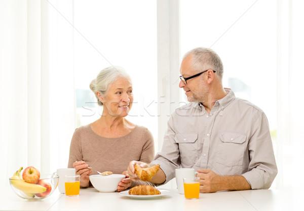 happy senior couple having breakfast at home Stock photo © dolgachov