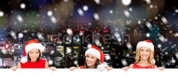 women in santa helper hat with blank white board Stock photo © dolgachov