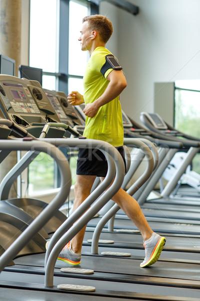 человека смартфон бегущая дорожка спортзал спорт Сток-фото © dolgachov