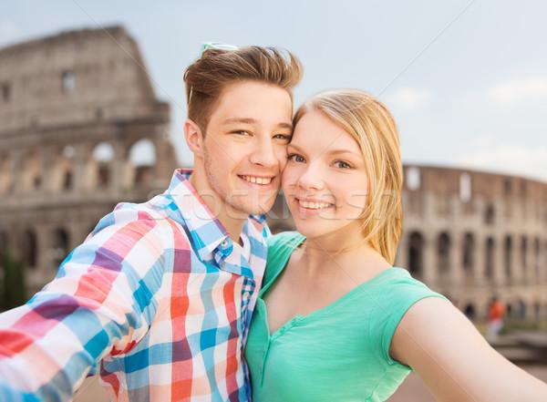 smiling couple taking selfie over coliseum Stock photo © dolgachov