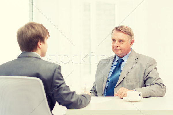 older man and young man signing papers in office Stock photo © dolgachov
