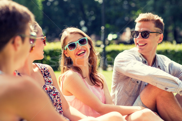 group of smiling friends outdoors sitting in park Stock photo © dolgachov