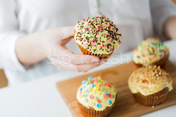 close up of woman with glazed cupcakes or muffins Stock photo © dolgachov