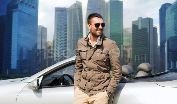 happy man near cabriolet car over city background Stock photo © dolgachov