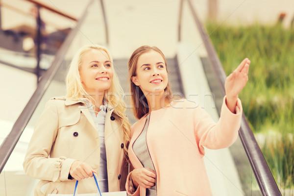Jeunes femmes pointant doigt escalator Mall vente Photo stock © dolgachov