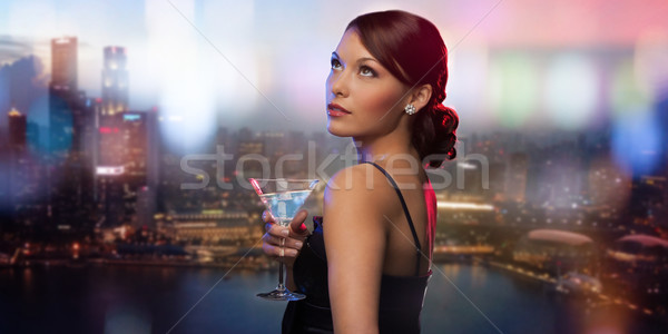 smiling woman holding cocktail over night city Stock photo © dolgachov