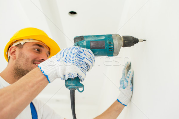 builder in hardhat with drill perforating wall Stock photo © dolgachov