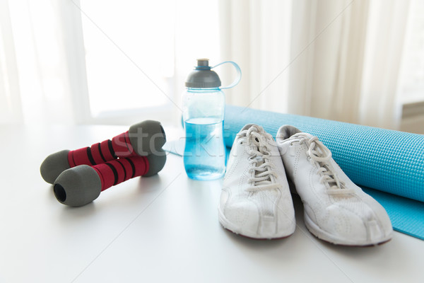close up of bottle, dumbbells, sneakers and mat Stock photo © dolgachov