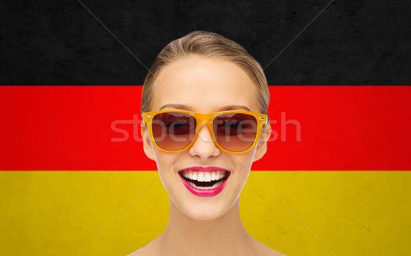 happy young woman in sunglasses over german flag Stock photo © dolgachov