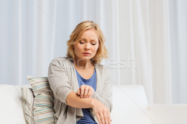 unhappy woman suffering from hand inch at home Stock photo © dolgachov
