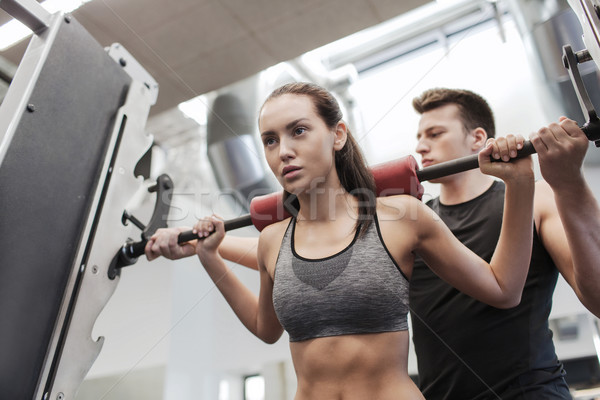 man and woman with barbell flexing muscles in gym Stock photo © dolgachov