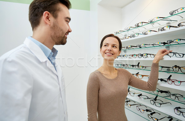 woman showing glasses to optician at optics store Stock photo © dolgachov