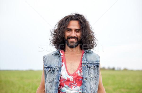Mosolyog fiatal hippi férfi zöld mező Stock fotó © dolgachov