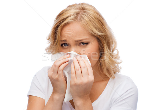 unhappy woman with paper napkin blowing nose Stock photo © dolgachov