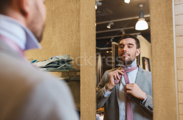 man tying tie on at mirror in clothing store Stock photo © dolgachov
