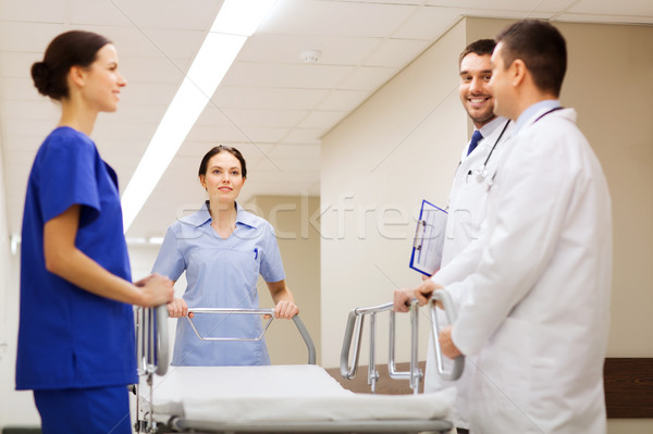 group of happy doctors with gurney at hospital Stock photo © dolgachov