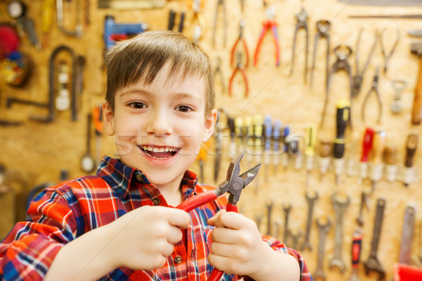 happy little boy with pliers at workshop Stock photo © dolgachov