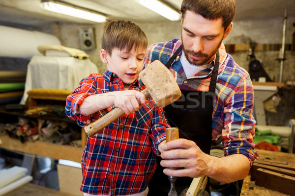 father and son with chisel working at workshop Stock photo © dolgachov
