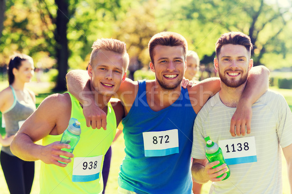 happy friends with racing badge numbers and water Stock photo © dolgachov