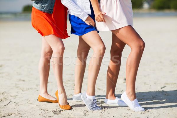 close up of women legs posing on beach Stock photo © dolgachov