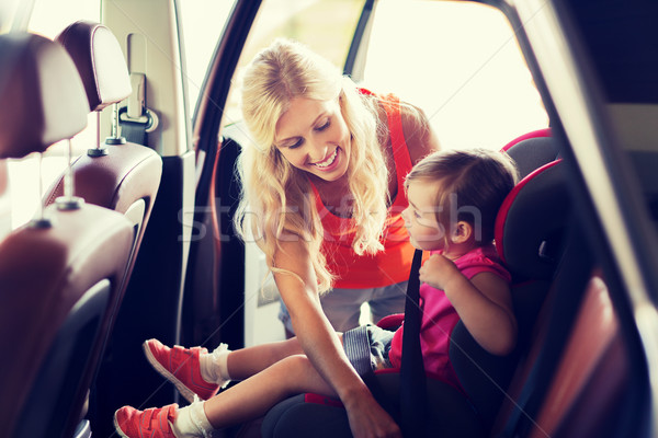 happy mother fastening child with car seat belt Stock photo © dolgachov
