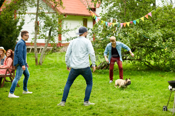 happy friends playing with dog at summer garden Stock photo © dolgachov