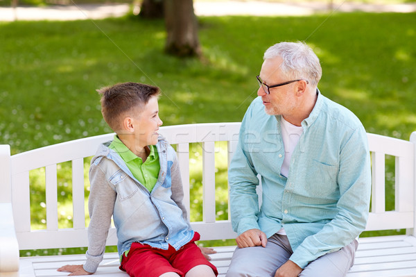 grandfather and grandson talking at summer park Stock photo © dolgachov
