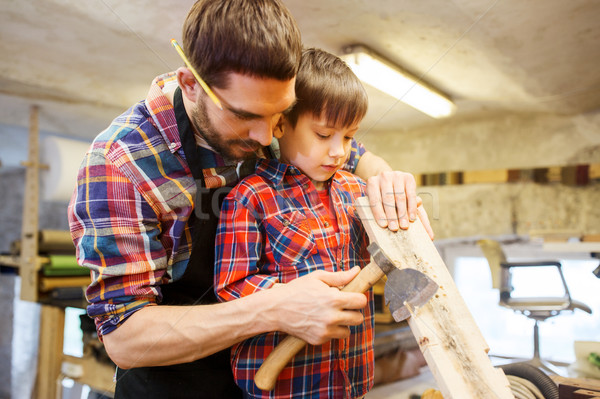 father and son with ax and wood plank at workshop Stock photo © dolgachov