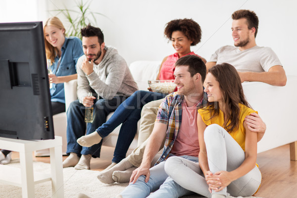 Stock photo: happy friends with popcorn watching tv at home