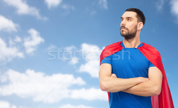 man in red superhero cape over blue sky Stock photo © dolgachov
