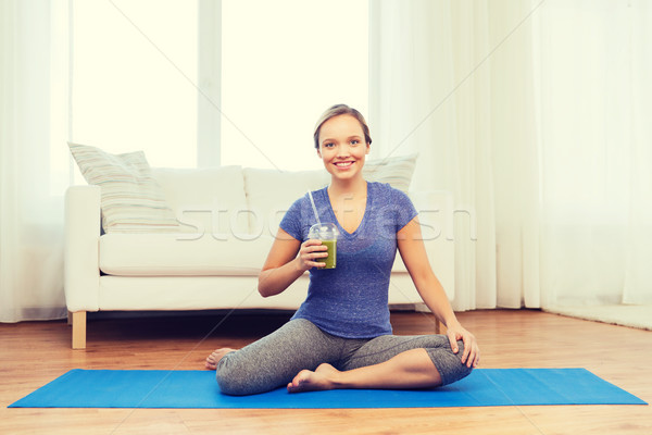 Stock photo: happy woman with smoothie sitting on mat at home