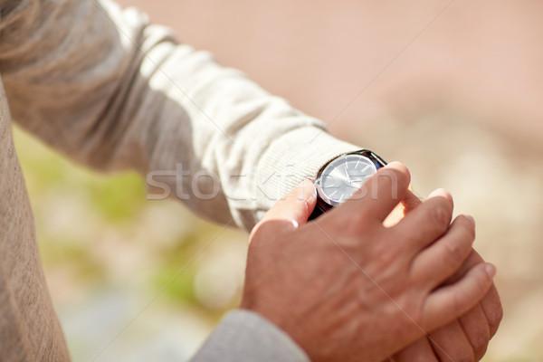senior man checking time on wristwatch outdoors Stock photo © dolgachov