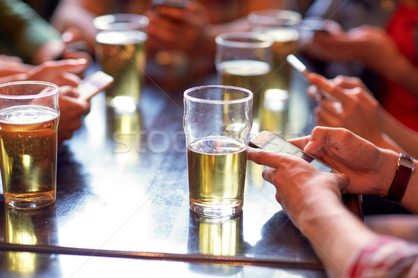 friends with beer and smartphones at bar or pub Stock photo © dolgachov