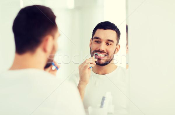 Hombre cepillo de dientes limpieza dientes bano Foto stock © dolgachov
