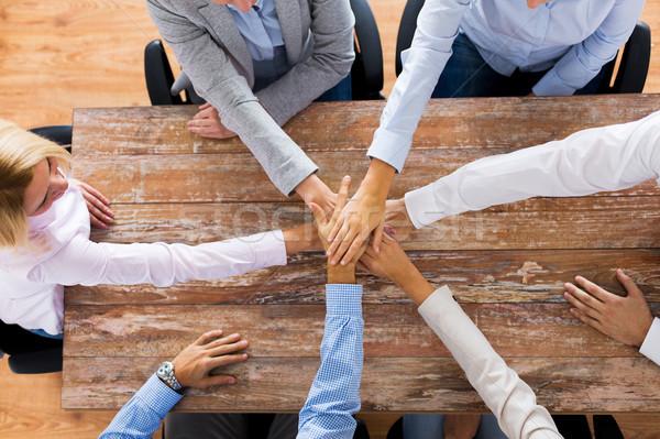 Ludzi biznesu trzymając się za ręce biuro tabeli działalności zespołowej Zdjęcia stock © dolgachov