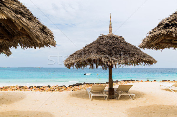 palapa and sunbeds on exotic tropical beach Stock photo © dolgachov