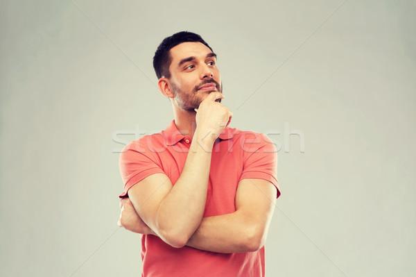 man in polo t-shirt thinking over gray background Stock photo © dolgachov
